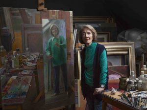 Portrait artist June Mendoza standing by her easel in her studio photographed by Aliona Adrianova