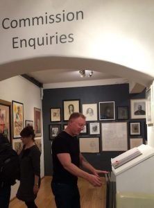 Browsing portfolios at the Annual Portrait Exhibition